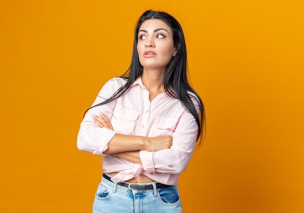Belle jeune femme en vêtements décontractés regardant de côté avec une expression sceptique avec les bras croisés debout sur un mur orange