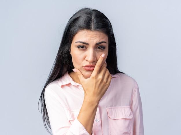 Belle jeune femme en vêtements décontractés regardant avec la main sur son menton pensant avec un visage sérieux