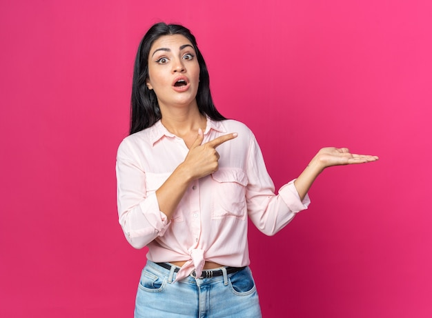 Belle jeune femme en vêtements décontractés surpris pointant avec l'index sur le côté présentant quelque chose avec le bras de sa main debout sur rose