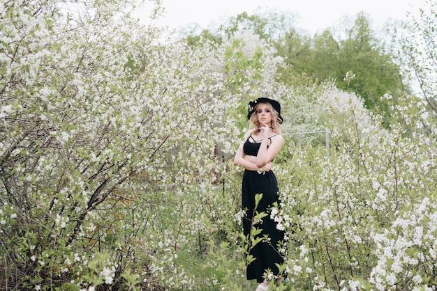 Une belle jeune femme en vêtements noirs et un chapeau dans un jardin fleuri au printemps 1