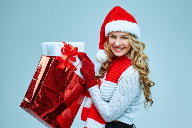 Belle jeune femme en vêtements de père noël avec un cadeau sur fond gris