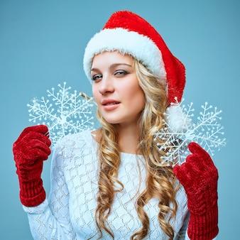 Belle jeune femme en vêtements de père noël avec des flocons de neige sur fond bleu