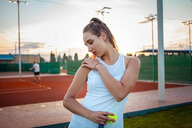 Belle jeune femme en vêtements de sport blancs posant avec des balles de tennis à la cour