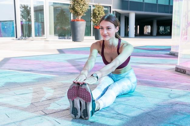 Belle jeune femme en vêtements de sport faisant des exercices d'étirement