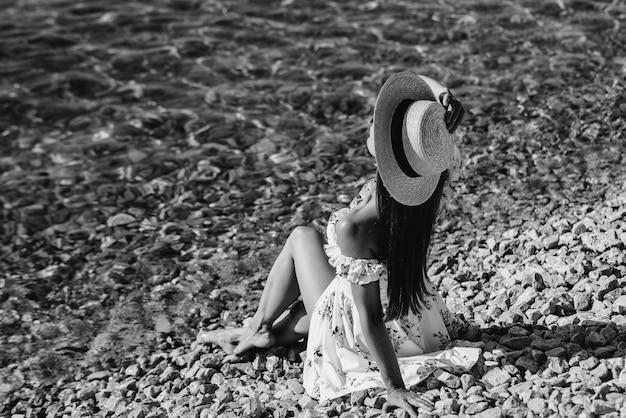 Une belle jeune femme vêtue d'un chapeau et d'une robe légère marche le long du rivage de l'océan sur fond d'énormes rochers par une journée ensoleillée. tourisme et voyages de vacances. noir et blanc.