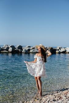 Une belle jeune femme vêtue d'un chapeau et d'une robe légère marche le long du rivage de l'océan sur fond d'énormes rochers par une journée ensoleillée. tourisme et voyages de vacances.
