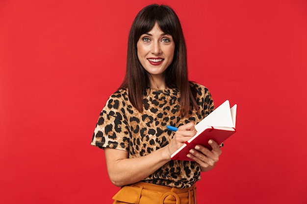 Belle jeune femme vêtue d'une chemise imprimée d'animaux posant isolée sur un mur rouge, écrivant des notes dans un cahier.