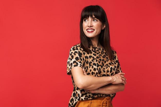 Belle jeune femme vêtue d'une chemise imprimée d'animaux posant isolée sur un mur rouge.