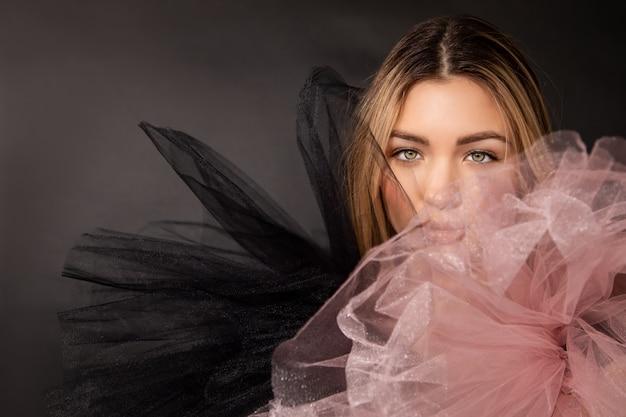Belle jeune femme vêtue de maquillage et robe de soirée en maille tout en posant