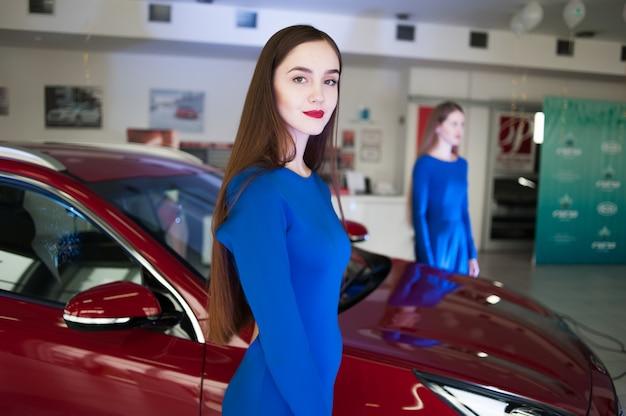 Belle jeune femme vêtue d'une robe au salon de l'automobile