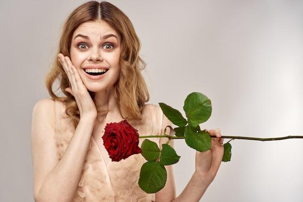 Belle jeune femme vêtue d'une robe délicate avec une rose écarlate à la main