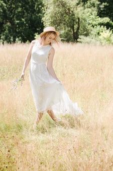 Belle jeune femme vêtue d'une robe en dentelle blanche avec des cheveux roses et un chapeau traverse le pré