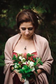 La belle jeune femme vêtue d'une robe de mariée avec un bouquet