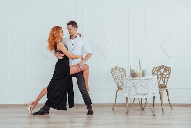 Belle jeune femme vêtue d'une robe noire et un homme en chemise blanche dansant.