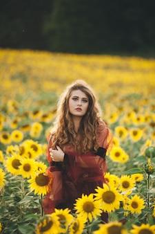 Belle jeune femme vêtue d'une robe parmi les tournesols en fleurs. agro-culture.
