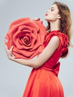 Belle jeune femme vêtue d'une robe rouge avec une grande fleur rose