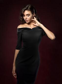 Belle jeune femme vêtue d'une robe de soirée noire posant sur fond rouge foncé