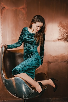Belle jeune femme vêtue d'une robe en velours, assise sur une chaise en cuir marron