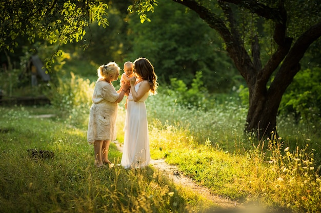 Belle jeune femme et vieille femme jouent avec un petit enfant en plein air