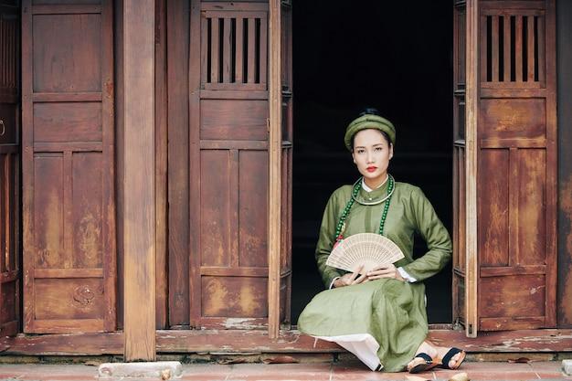 Belle jeune femme vietnamienne en costume traditionnel tenant un ventilateur en bois lorsqu'elle est assise sur le porche de la vieille maison