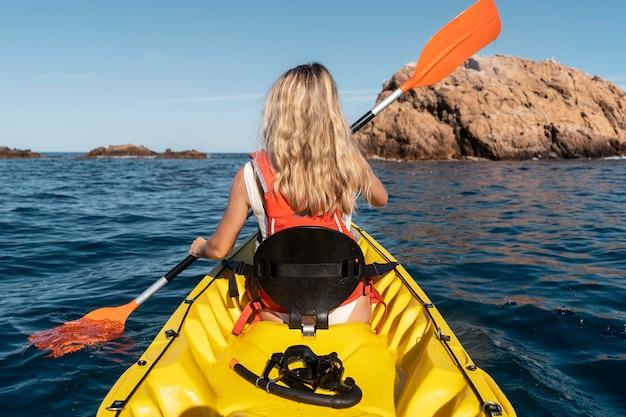 Belle jeune femme voyageant en canoë
