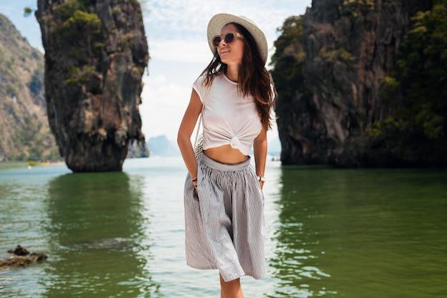 Belle jeune femme voyageant en thaïlande, vacances d'été, style décontracté, lunettes de soleil, chapeau, jupe en coton, t-shirt, souriant, heureux, aventures