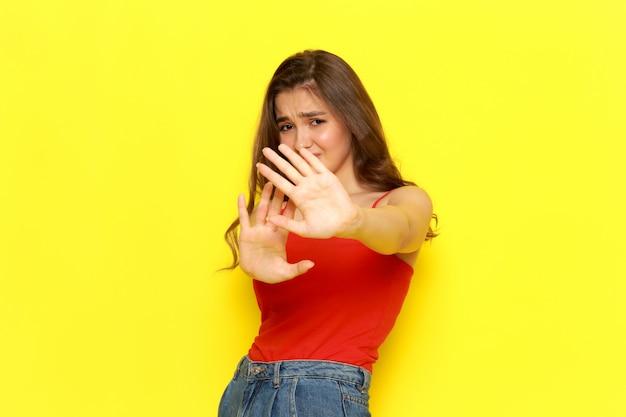Une belle jeune femme vue de face en chemise rouge et jean bleu posant avec une expression prudente