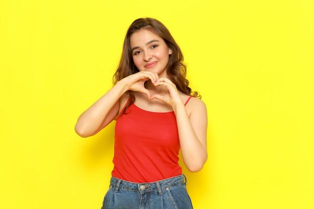 Une belle jeune femme vue de face en chemise rouge et jean bleu souriant et montrant un signe d'amour
