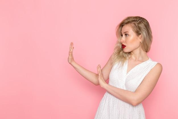 Une belle jeune femme vue de face en robe blanche posant avec une expression prudente