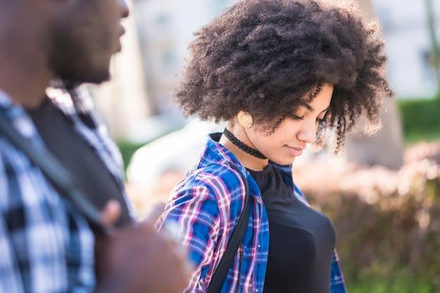 Belle jeune fille afro-américaine bouclée noire marchant dehors avec son petit ami afro