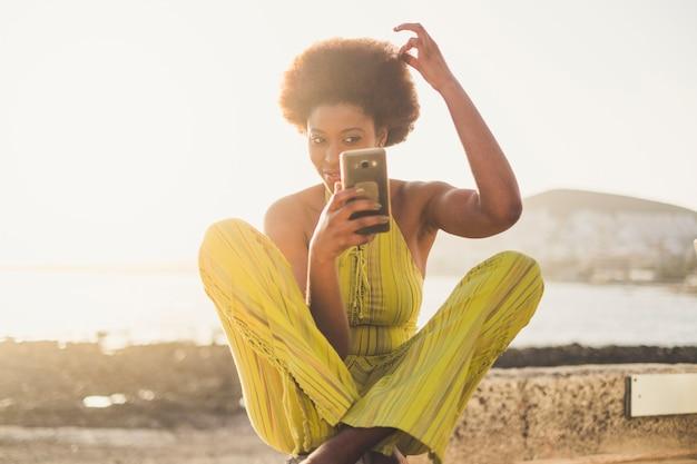 Belle jeune fille afro de race noire prend soin et vérifie ses cheveux africains traditionnels à l'aide d'un téléphone intelligent moderne comme un miroir pour se voir. gens modernes du millénaire utilisant le concept technologique