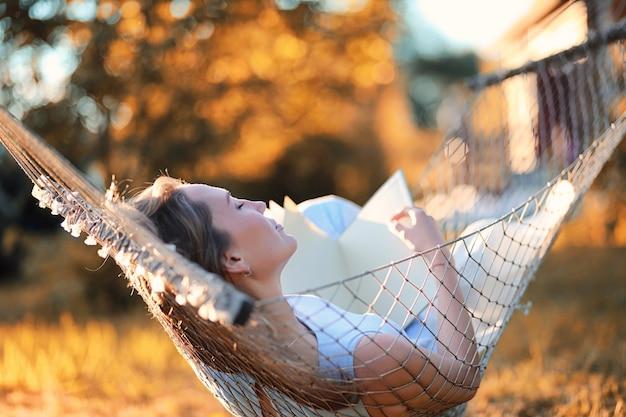 Belle jeune fille allongée et lisant un livre à l'automne en plein air
