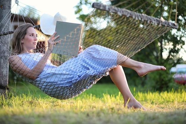 Belle jeune fille allongée et lisant un livre en été à l'extérieur