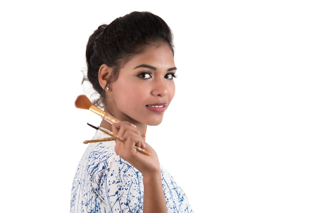 Belle jeune fille appréciant avec des pinceaux de maquillage isolés sur blanc