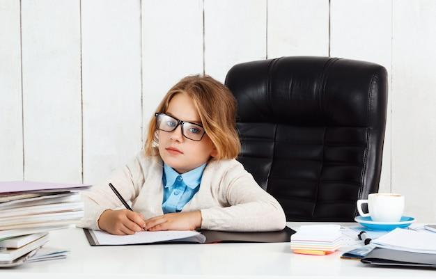 Belle jeune fille assise au lieu de travail au bureau.