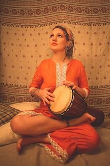 Belle jeune fille assise dans le yoga et la méditation pose avec un tambour