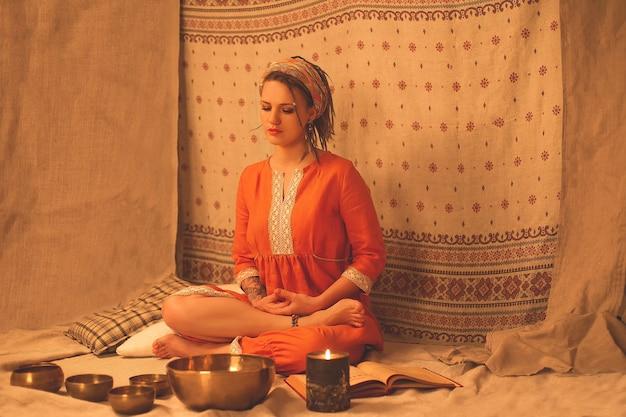 Belle jeune fille assise en position de yoga et de méditation avec des bols et des bougies