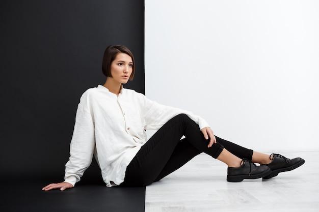 Belle jeune fille assise sur le sol sur un mur noir et blanc