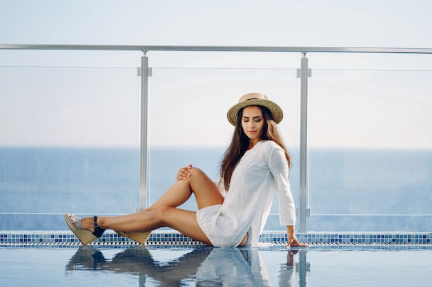 Une belle jeune fille assise sur une terrasse d'été et en regardant l'océan