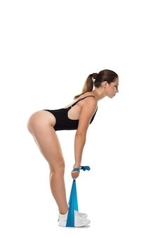 Belle jeune fille athlétique au corps noir faisant des exercices de force avec du caoutchouc élastique isolé sur fond blanc