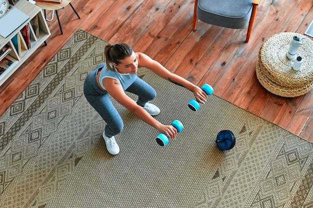Belle jeune fille athlétique en leggings et haut s'accroupit avec des haltères à la maison. sport, mode de vie sain.