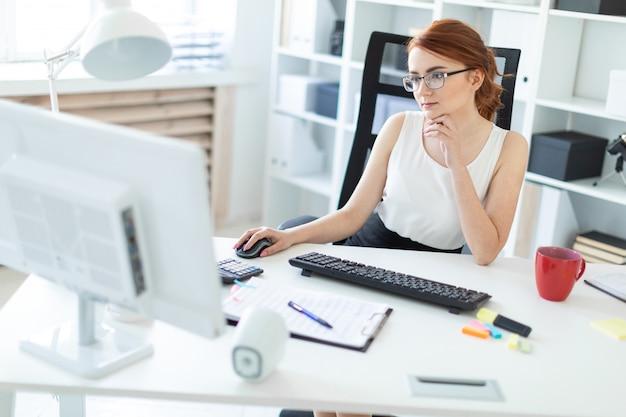 Belle jeune fille au bureau travaillant à l'ordinateur.