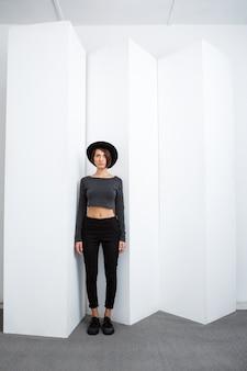 Belle jeune fille au chapeau noir posant sur un mur blanc