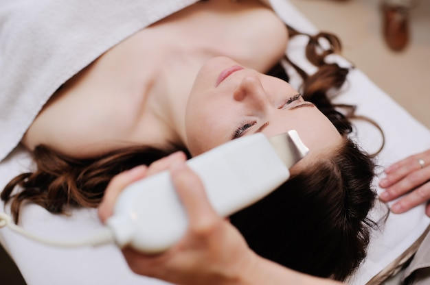 Belle jeune fille au salon spa. cosmétologie du matériel