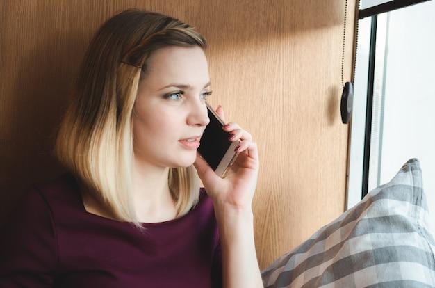 Belle jeune fille aux cheveux blonds souriant parlant sur un téléphone mobile