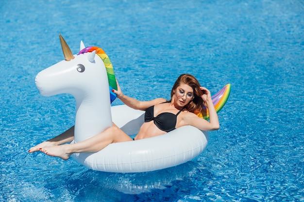 Belle jeune fille aux cheveux bruns avec une bonne silhouette bronzée dans la piscine