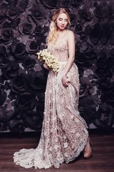 Belle jeune fille aux cheveux bruns portant une robe beige luxueuse,