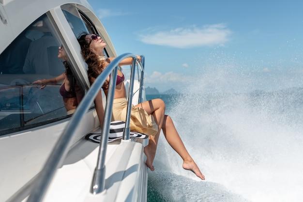 Belle jeune fille aux cheveux longs, assis sur la proue du yacht en jupe blanche et bikini