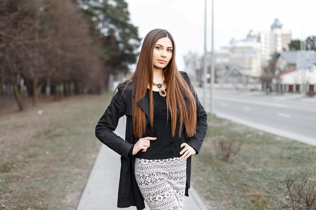 Belle jeune fille aux cheveux longs dans un élégant manteau noir