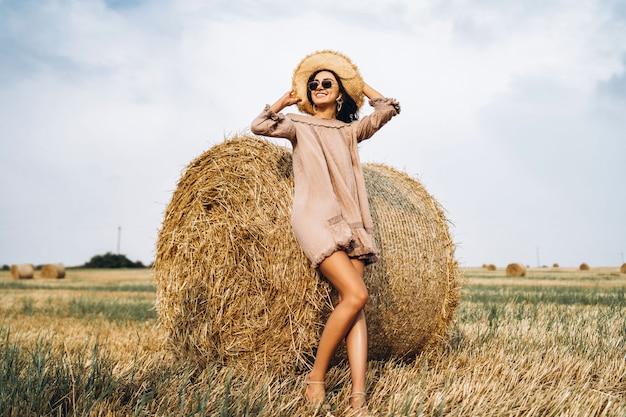 Belle jeune fille aux cheveux longs en lunettes de soleil et chapeau de paille posant sur un champ de blé près de balles de foin.